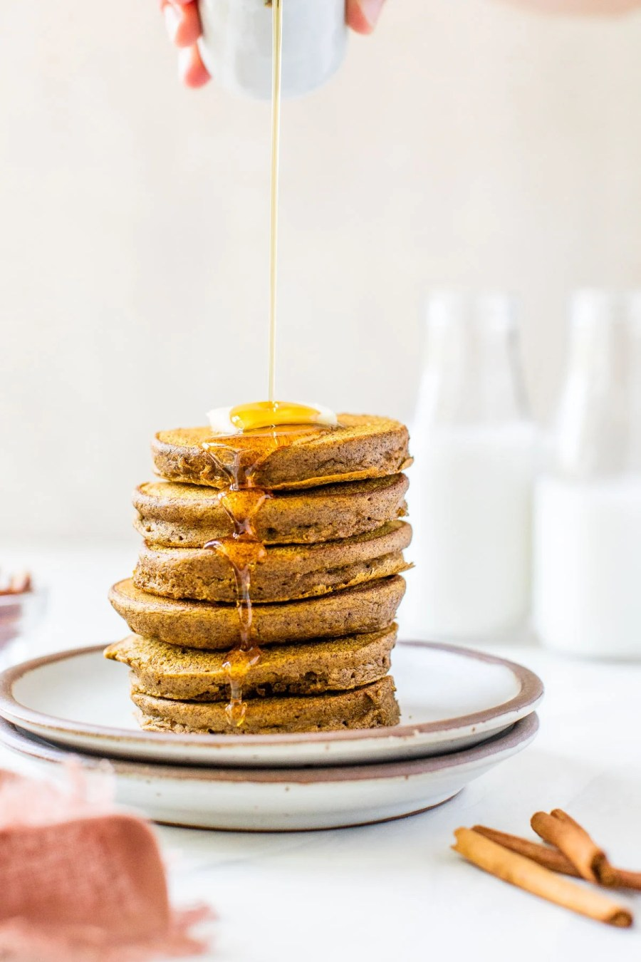 a stack of fluffy gluten free pumpkin pancakes in a stack with maple syrup