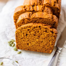 slices of low fat pumpkin bread on a piece of white parchment baking paper with a knife and pumpkin seeds