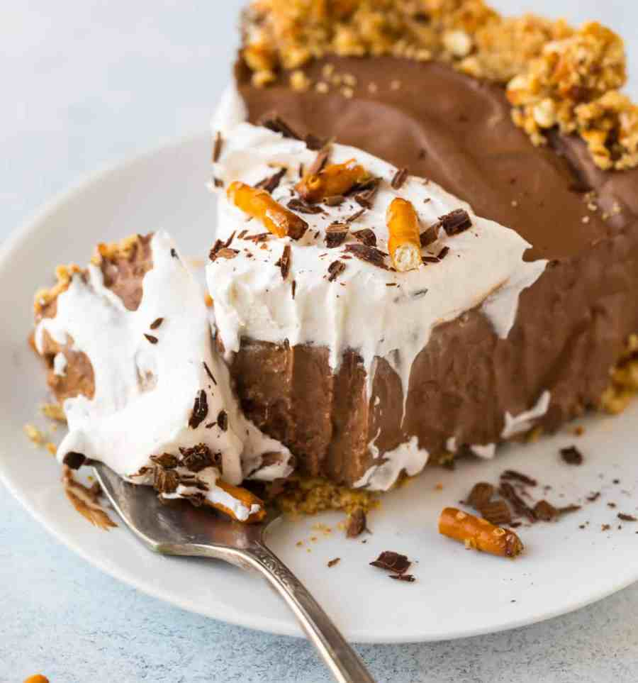 Decadent vegan chocolate mousse pie with a no bake filling and pretzel crust on a plate with a fork and whipped coconut cream