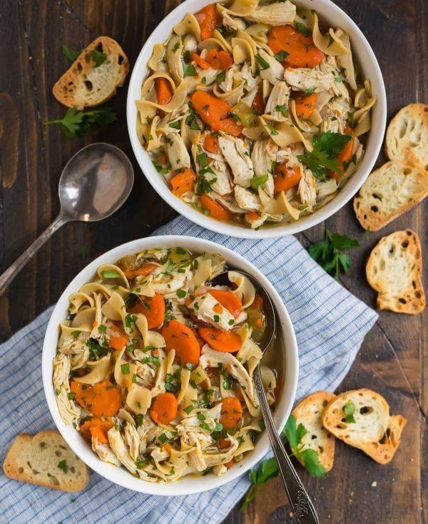Two bowls of cozy chicken soup with veggies and noodles