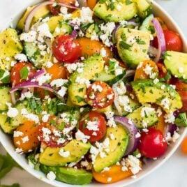 A white bowl full of avocado tomato salad