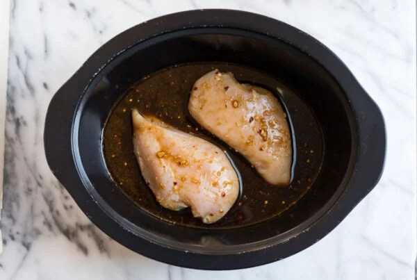 A crockpot with two chicken breasts topped with an Asian ginger soy sauce