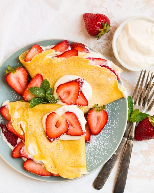Strawberry Cream Cheese Crepes on a plate with powdered sugar