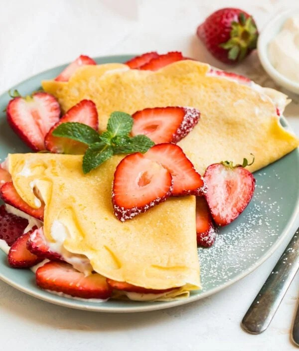 A plate with two strawberry crepes topped with sliced berries and cream