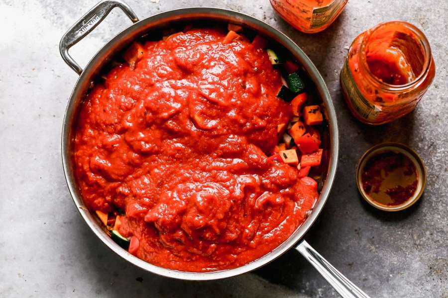 Tomato sauce poured over a pan of vegetables