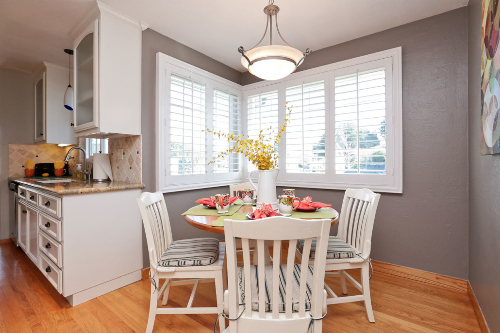 breakfast nook with white furniture and dark gray paint