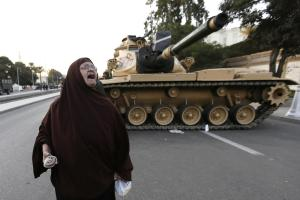 Eine Demonstrantin geht in Kairo an den Panzern vorbei, die den Präsidentenpalast schützen