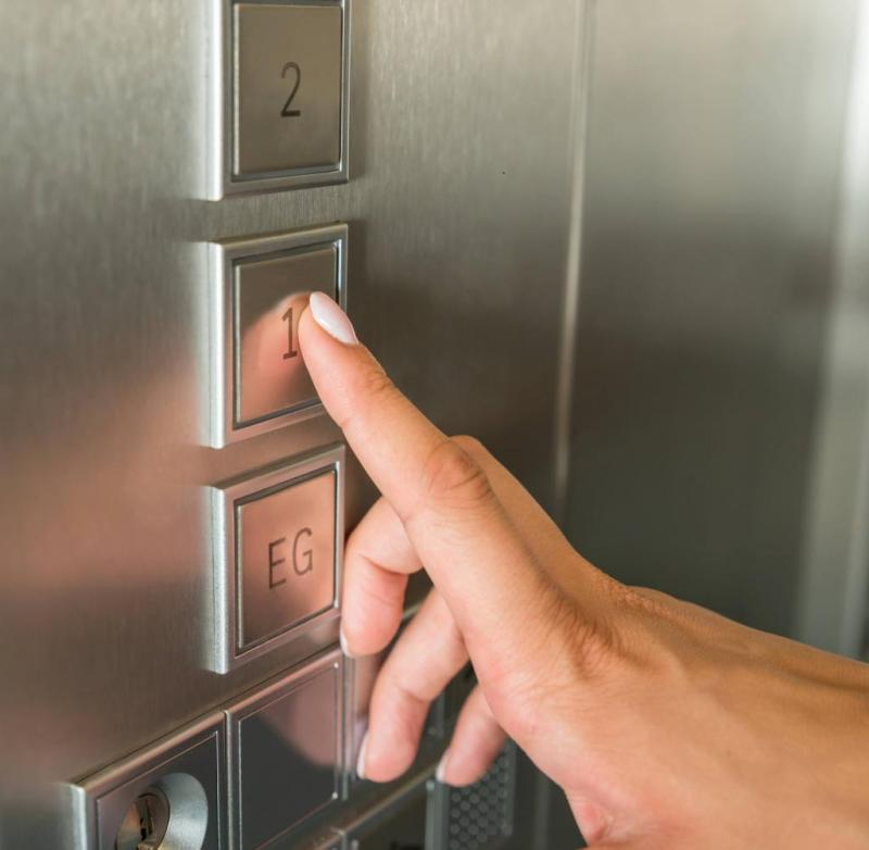 A woman presses a button in the elevator (symbol photo)