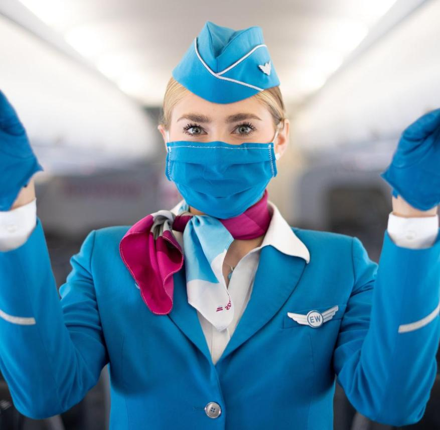 A flight attendant demonstrates the security measures to protect against infection with Corona