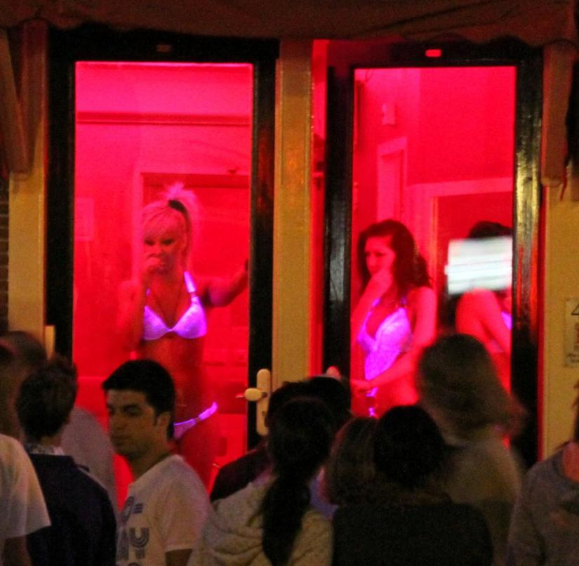 Amsterdam (Netherlands): Tourists crowd in the red light district in front of a shop window with prostitutes