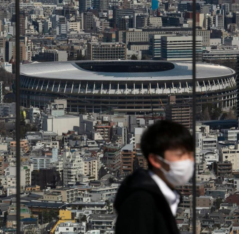 A man is wearing a face mask and is standing on a viewing platform.  In the background you can see the new national stadium, where the opening ceremony of the 2020 Olympic Games was to take place.