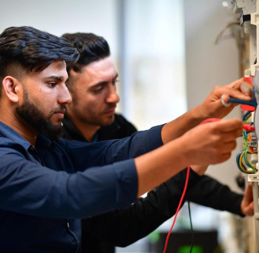 GARBSEN, GERMANY - APRIL 26: Sheraz Chaudry (L), a refugee from Pakistan who came to Germany in 2015, attends a job training program as a electrical engineer at Campus Handwerk on April 26, 2019 in Garbsen, Germany. According to federal statistics 361,000 people from countries of origin of many of Germany's refugees had a job in 2018. And the number of refugees with jobs subject to social insurance contributions rose from 203,000 in 2017 to 298,000 in 2018. The same study claims German language deficiency remains the biggest barrier for many refugees to find a job. Germany took in over one million refugees, from countries including Syria, Afghanistan, Eritrea, Pakistan, Iran and Iraq, in 2015-2016. (Photo by Alexander Koerner/Getty Images) Getty ImagesGetty Images