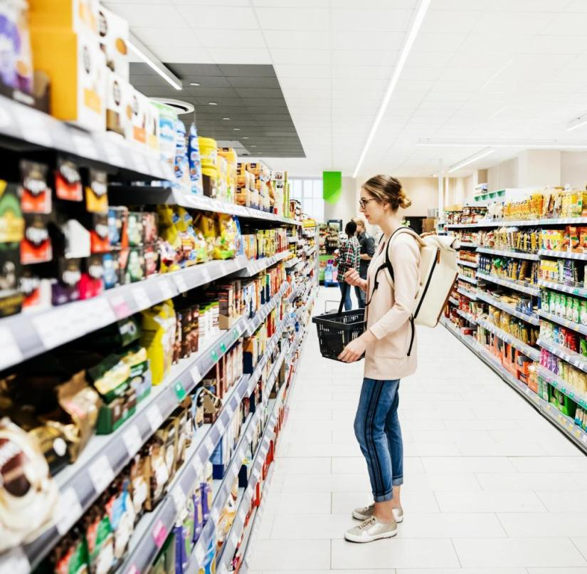 A colorful supermarket aisle with people shopping for groceries. Getty ImagesGetty Images
