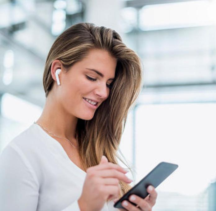 Woman with smartphone and AirPods