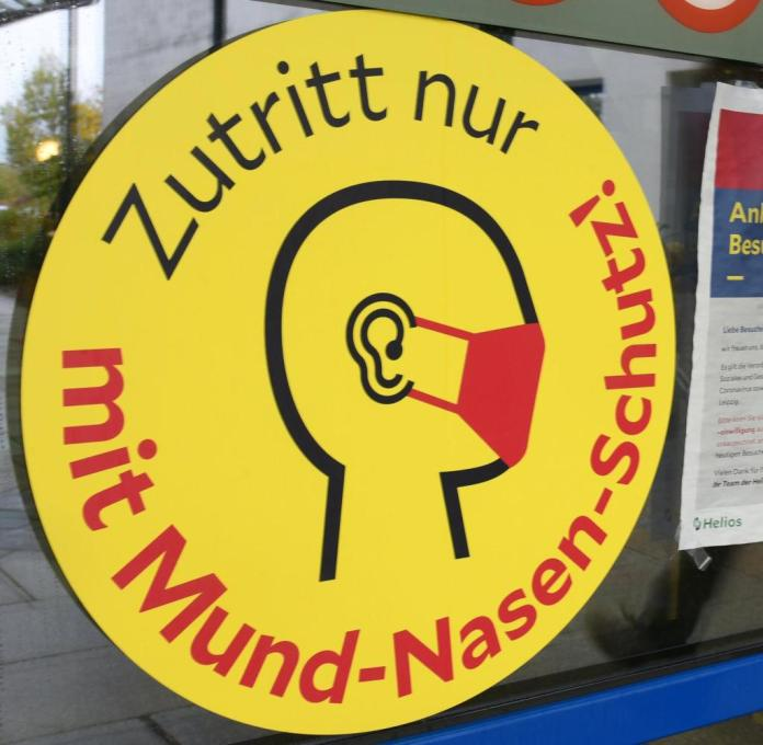 A large sign at the entrance to a clinic in Leipzig indicates that a mask is required.