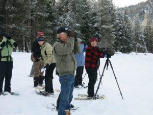 Using snowshoes, Heather Murphy (at scope) leads volunteers conducting a bird survey at Lake Wenatchee.