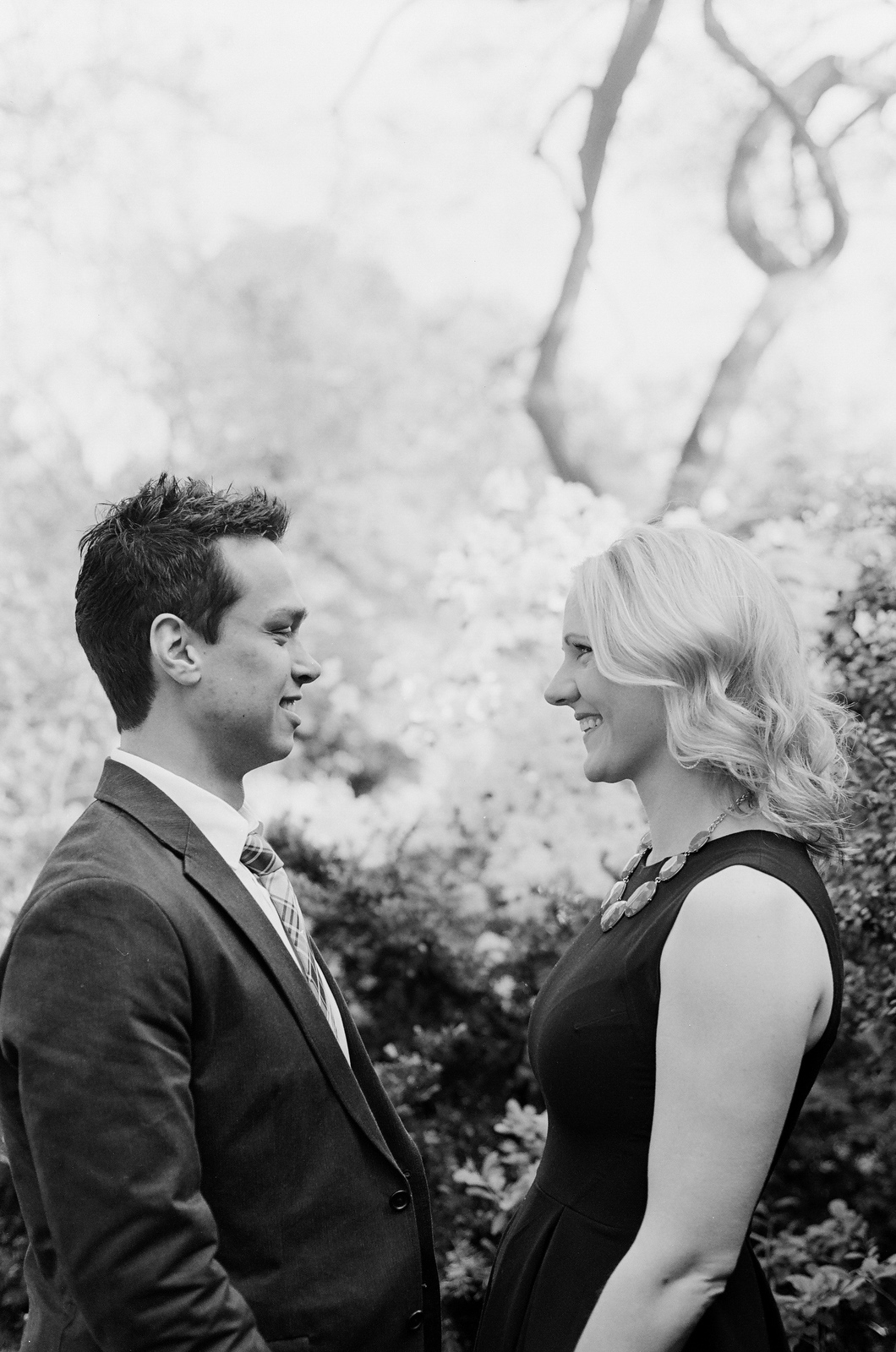 black and white photo of engaged couple smiling at each other wendy g photography