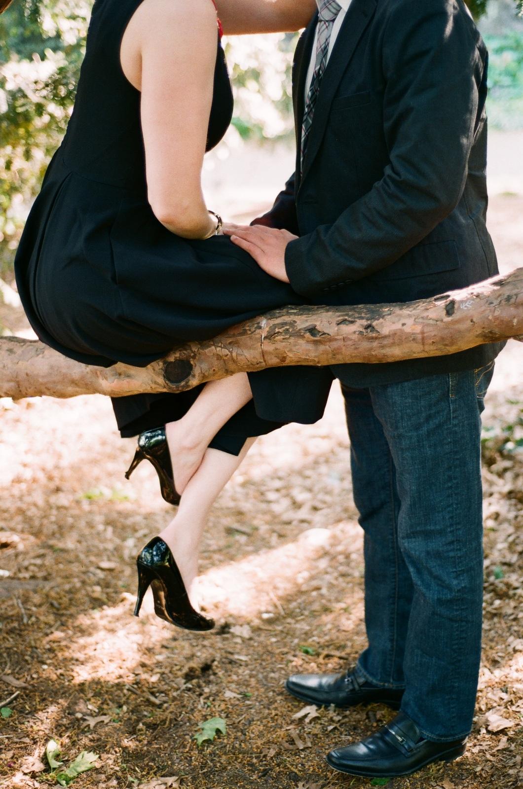 fine art portrait of engaged couple leaning on tree limb