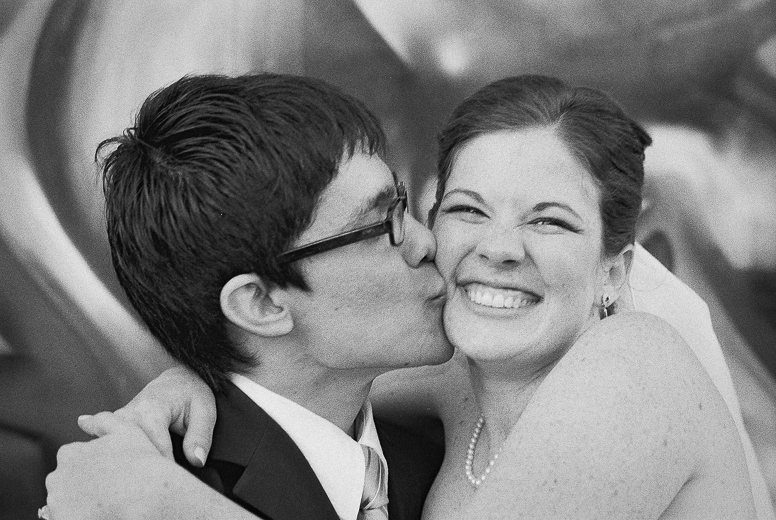 groom kissing bride black and white graffiti