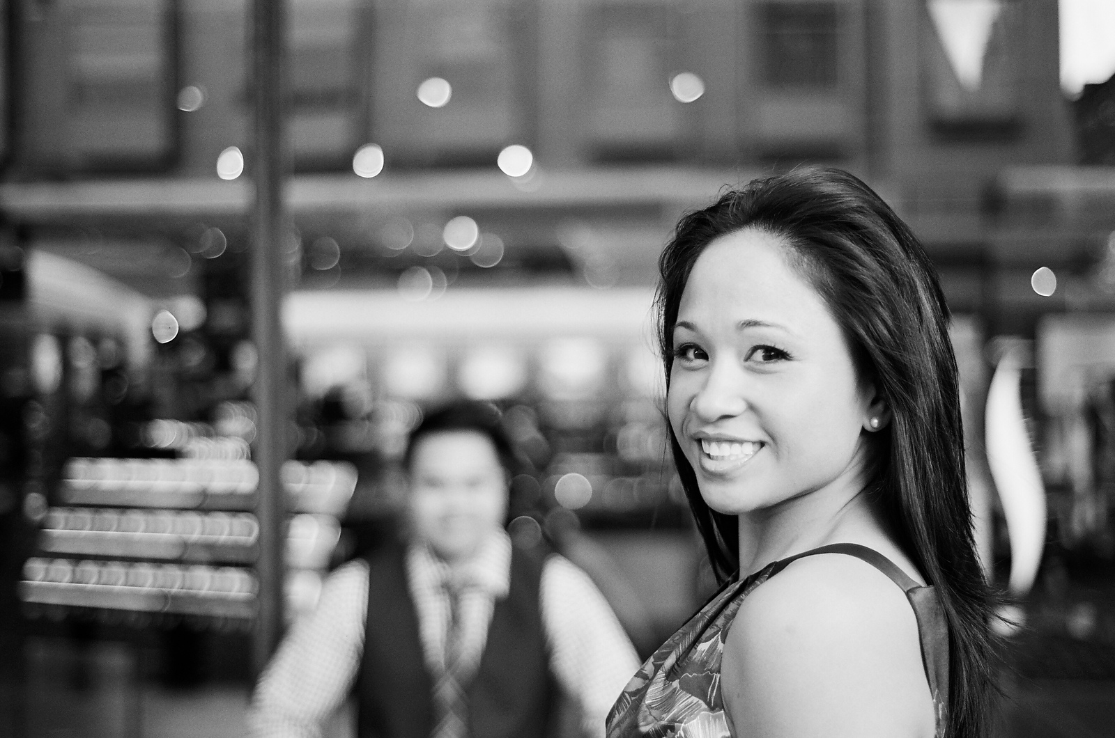 black and white photo of engaged nyc couple with groom in background