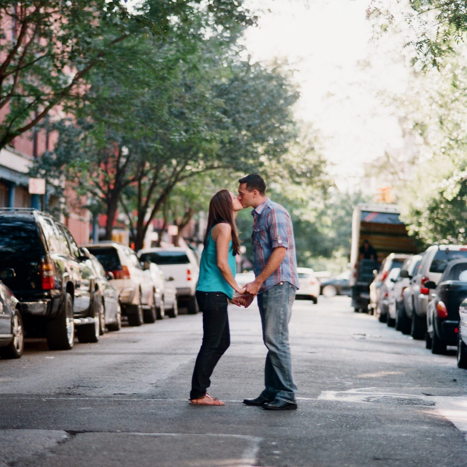engaged couple in downtown nyc standing in middle of street kissing