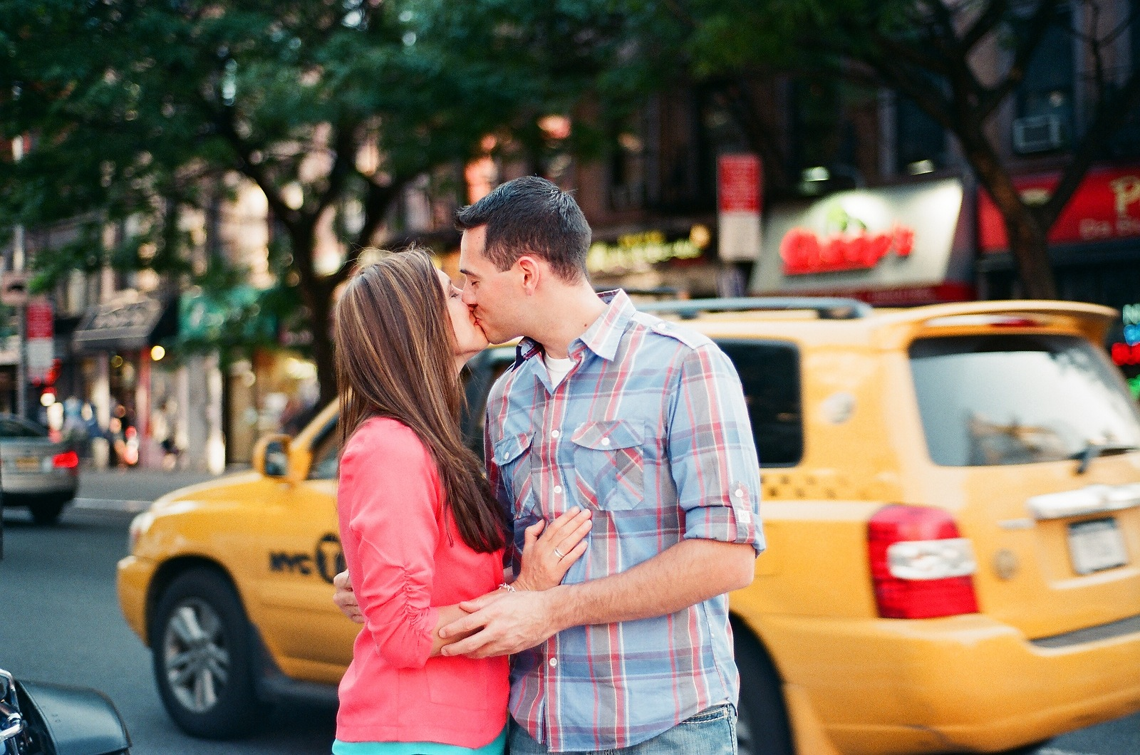 couple kissing with yellow cab in background