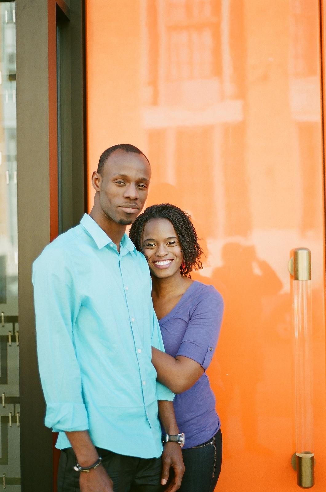 engaged couple bride leaning onto groom orange background