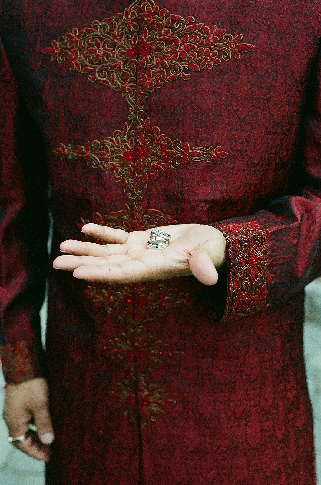 groom holding wedding bands in palm of hand