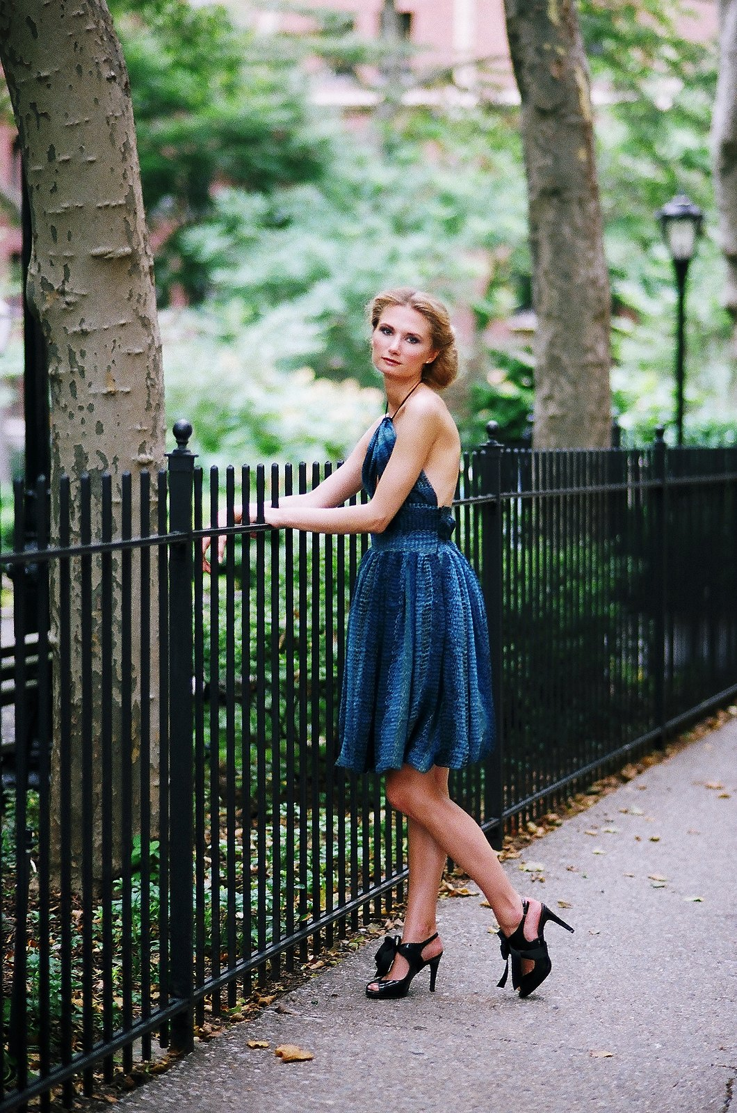 short blue toned dress with woman leaning on iron fence posing