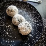 3 oreo balls on a plate with powdered sugar
