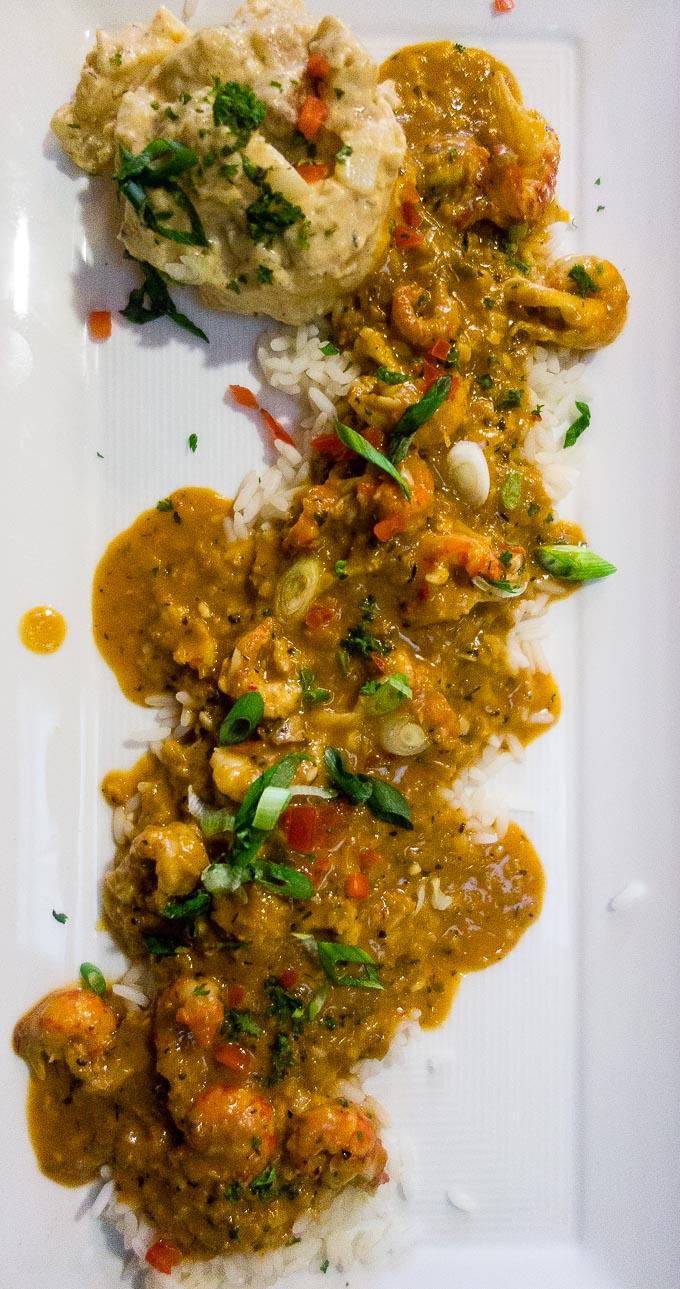best cajun food in downtown san diego, crawfish etouffee over rice on a plate with cajun potato salad