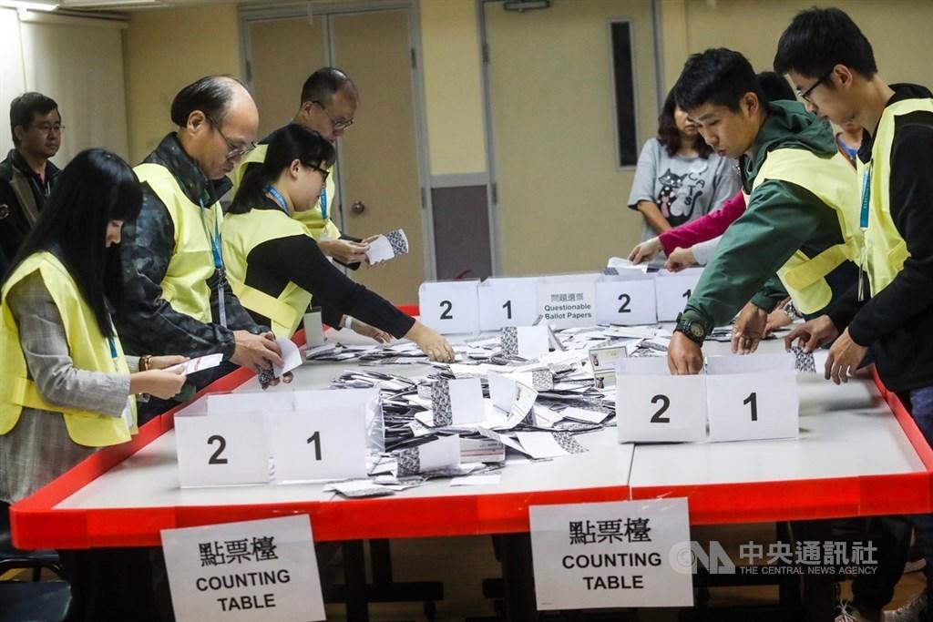 香港近日抗爭情勢逐漸趨緩,24日區議會選舉如期舉行,晚間10時30分結束投票後進行點票作業,灣仔一家投票站工作人員25日凌晨仔細清點選票。中央社記者吳家昇攝 108年11月25日