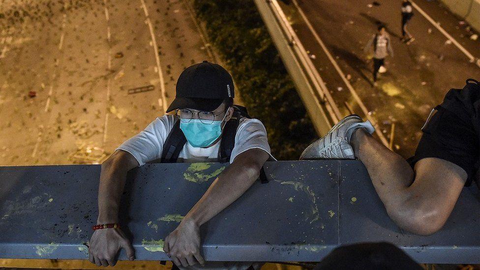 示威者试图从校园内行人天桥游绳逃至校外公路