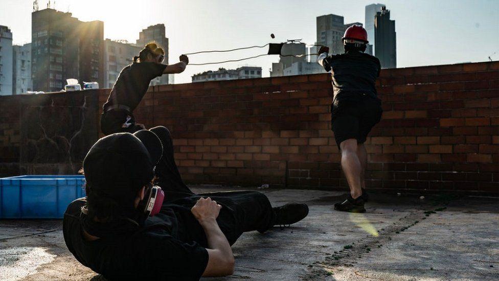 示威者使用弹弓发射砖块