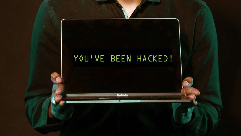 image showing a person holding a laptop that is hacked. Saefko: The crypto targeting trojan