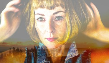 Photo of Jenn Grant. She has short blonde hair and bangs. She is staring just past the camera. The photo is double exposed and behind her we see a fading sunset.