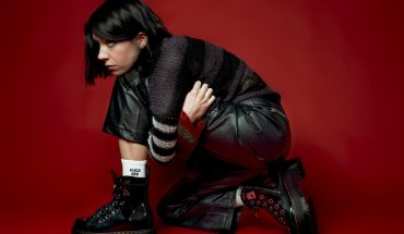 K Flay press photo. K Flay is sitting on the floor wearing all black in front of a red backdrop.