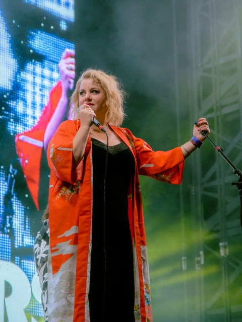 Amy Millan of the band Stars singing on stage. She is wearing a red kimono with a black dress underneath and looking away from the camera