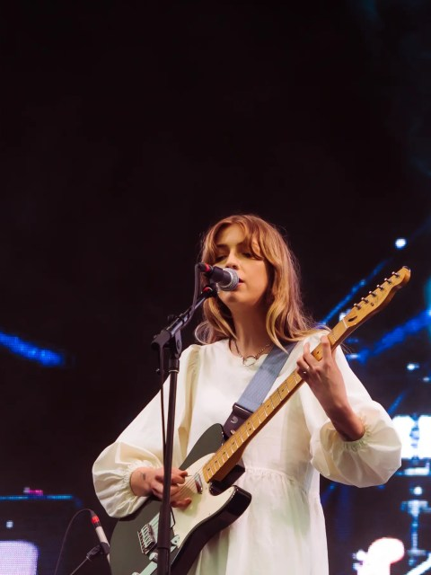 Singer songwriter Ellis is performing on stage. She is wearing a white dress and singing into a microphone. She is playing a black and white electric guitar.
