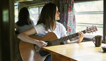Caroline Marie Brooks press photo. Caroline is sitting by a window playing the guitar.