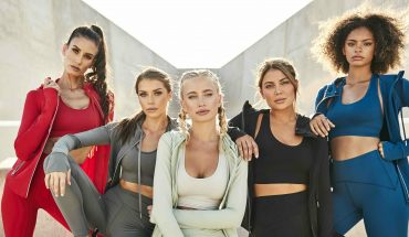Five women are standing together wearing V Shred Fitness Apparel. They are wearing running jackets, sports bras, and yoga pants in red, grey, green, black, and blue.