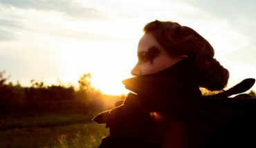 Emma Cook is standing in a field at sunrise. The sun is rising behind her. She is looking to the left and has her back facing away from the camera.