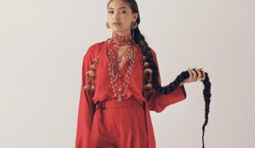 Joy Crookes press photo. Joy is waring an orange jumpsuit and standing in front of a beige backdrop.