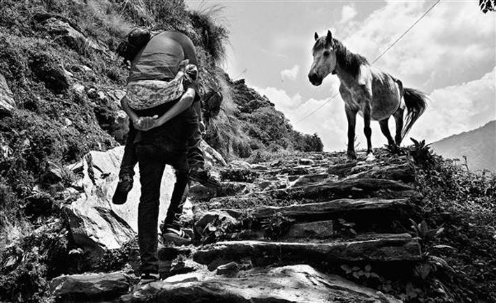 Nepal, maggio 2015. Hem Gurung segretario generale della Ils affetto da poliomelite viene portato a spalla sui sentieri della riserva naturale dell'Annapurna. Foto di Christian Tasso