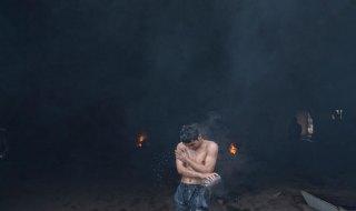 Belgrado, Serbia. Un uomo si lava con dell'acqua calda al di fuori di un deposito ferroviario in disuso usato dai rifugiati e dai migranti come riparo  - Photo credit: Marko Drobnjakovic