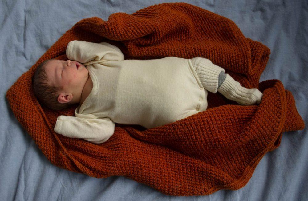 Selbstgestrickte Babydecke im Perlmuster aus Baumwoll-Merinowoll ...