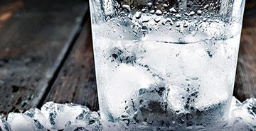 Glas mit Wasser und Eiswürfeln