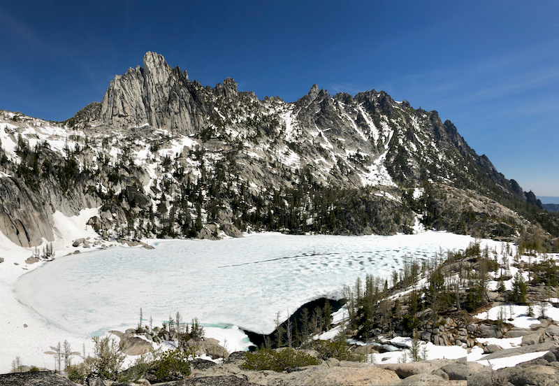 Snow-covered alpine lake below a jagged mountain peak