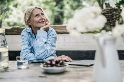 Mature woman sitting on terrace, with cherries on table