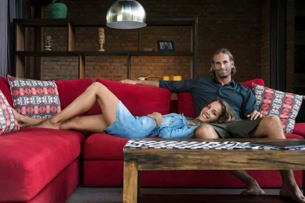 Smiling couple relaxing on red couch in modern living room